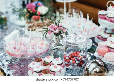 Candy bar covered with silver cloth and served with pink sweets and flowers