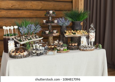 Candy bar for holiday celebration. Sweet buffet for birthday party or wedding. Desserts assortment against wooden background, catering concept
