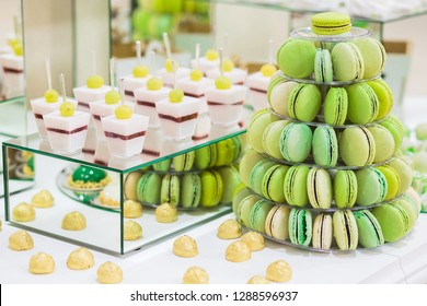 Candy bar with macarons, cakes, cake pops. Colorful green macaroons pyramide, close up.