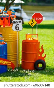 Candy bar on boy's birthday party with a lot of different candies, popcorn, beverages and big cake standing on a barrel. Decorated in bright colors. Hot wheels, cars or racing theme. Summer, outdoor