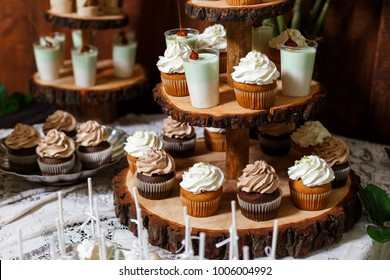 Candy bar on wooden wedding party with a lot of different candies, cupcakes, souffle and cakes. Decorated in brown and green colors, nature and eco theme, indoor