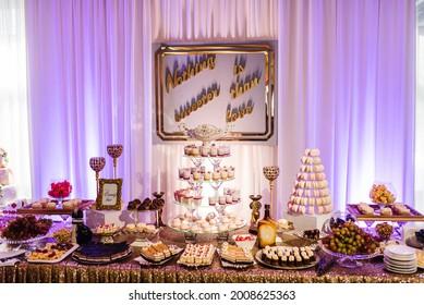 Süßigkeiten-Bar. Hochzeitskuchen mit Kerzen und festlichem Tisch mit Desserts.