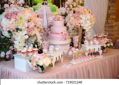 Candy bar and wedding cake. Table with sweets, buffet with cupcakes, candies, dessert.