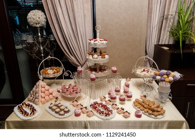 Candy bar/Wedding candy bar display featuring all sorts of delicious cookies and sweets arranged in special trays and supports.