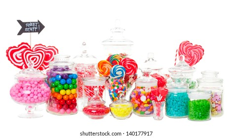 A candy buffet with a wide variety of candies in apothecary jars.  Shot on white background.