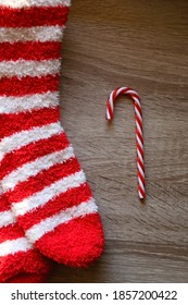 Candy cane decoration and striped fuzzy socks. Top view.