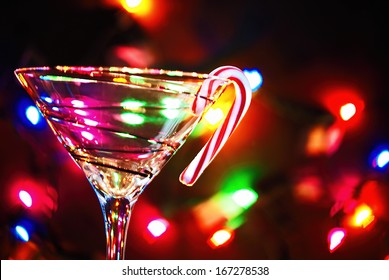 candy cane hooked on martini glass with bokeh lighting