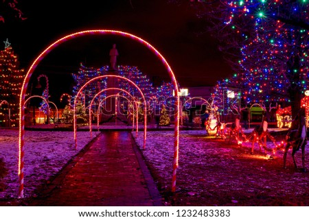 Candy cane lighted arches and a Santa with reindeer form part of a village  commons Christmas - Candy Cane Lighted Arches Santa Reindeer Stock Photo (Edit Now