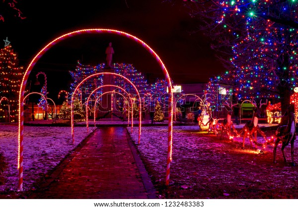 Candy cane lighted arches and a Santa with reindeer form part of a village commons Christmas display