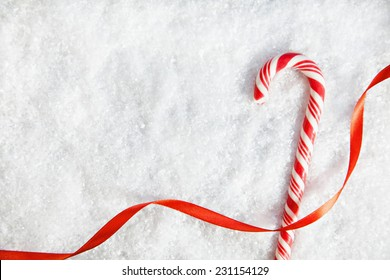 Candy Cane And Ribbon On Snowy Background. Copy Space