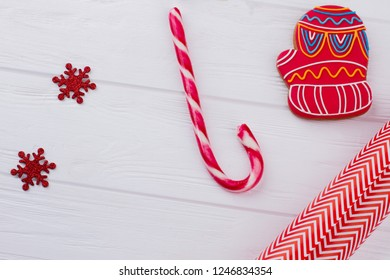 Candy cane, wrapping paper and decorations. Lollipop cane, gingerbread mitten, wrapping paper and decorative snowflakes. Christmas holiday celebration.