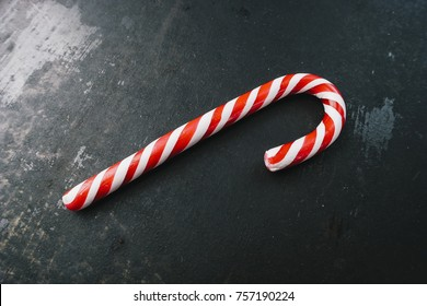 candy canes in Christmas colours on a dark surface