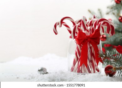Candy canes in glass jar and Christmas balls on table against light background. Space for text