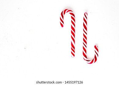 Candy canes on a white surface, top view, place for text
