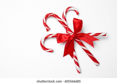 Candy canes with red bow on white background
