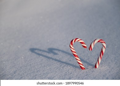 Candy canes in the shape of hearts are stuck in the snow. The sun is shining and a long shadow in the shape of a heart falls on the snow.