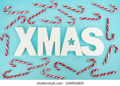 Candy Canes and wooden XMAS Letters on blue light background