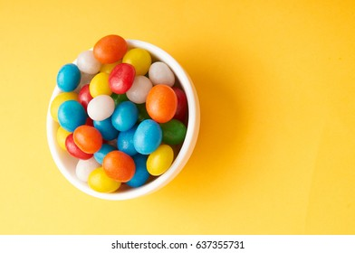 candy colored balls in a bowl  on yellow background