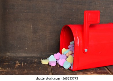 Candy conversation hearts spilling out of a red mailbox