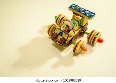 A candy and cookie car is built with a variety of confections including graham crackers, dots, oreos, frosting, and candy. Kids love the car and can eat it.