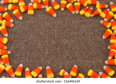 Candy Corn Framing Brown Tweed Fabric with center background space or room for your words, text, copy for Harvest Festival, Halloween or Thanksgiving