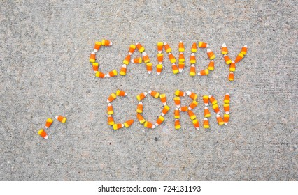 Candy corn spelled out on a sidewalk using candy corn.
