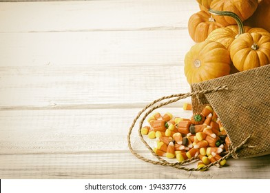 Candy Corn Spilling from Burlap Bag on Rustic White Wood Board Background with room or space for copy, text.   Horizontal, vintage sepia processing