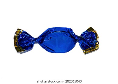 Candy in a dark blue shiny paper wrapper closeup