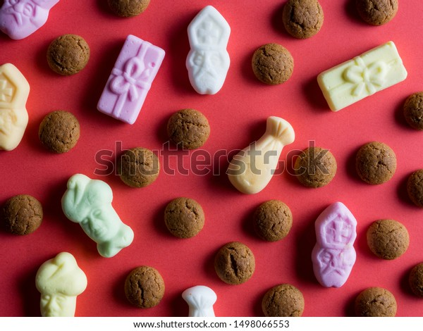 Candy for the Dutch holiday called Sinterklaas. With Dutch candy called Pepernoten and Schuimpjes. On a red background, top view.