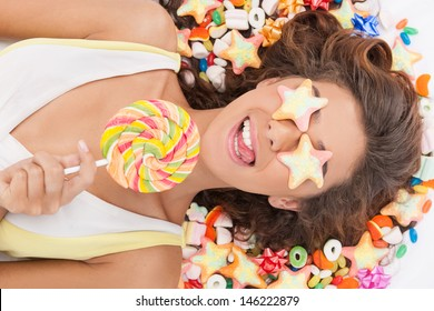 Candy girl. Top view of beautiful young women with candies covered her eyes holding a lollipop while lying on candies