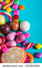 candy, gum, lollipops, marmalade and other sweets on blue background