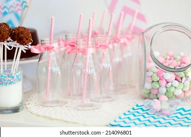 Candy jar and fancy milk bottles for drinks on a dessert table at party or wedding celebration