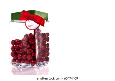 Candy jar with red glittery candy, green lid and gift tag isolated on white with copy space