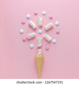 candy, marshmallow and ice cream waffle cone on pink background