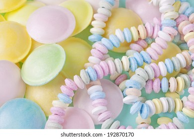 Candy necklace on a blue pastel colored background