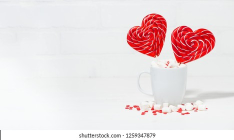 candy on a stick in the form of a heart in a cup of marshmallows on white background, horizontal