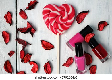 Candy on a stick in the form of the heart, the petals of dried flowers and nail polish: beauty, grooming, greeting card Happy Valentine's Day, International Women's Day (8 March), the day the mother