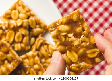 Candy with peanut, known as Pe de Moleque in Brazil and Chikki in India. Sweet food of Festa Junina, a typical brazilian party, holiday event in June. Hand picking up a snack.