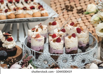 Candybar in a restaurant. Decorated white table fool of sweet pastry