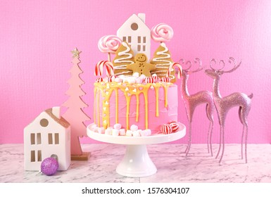 Candyland fairytale style children's party Christmas cake in pink and gold table setting with reindeer and village house decorations.