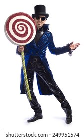 Candyman. Man wearing shiny vinyl pants and morning coat, top hat and goggles, holding giant lollipop.