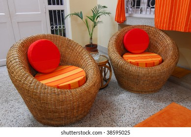Cane furniture chair with orange cushions home interior