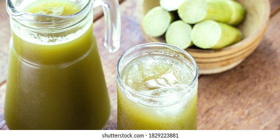 The cane juice or garapa is the liquid extracted from the sugar cane in the milling process. Sweetened, organic drink with pieces of cane in the background