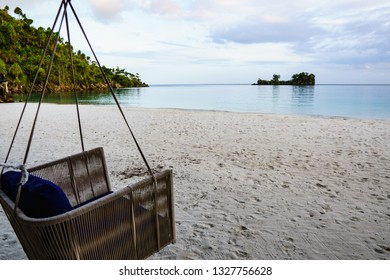 Cane swing with comfortable navy blue cushions looking out over a white sand beach and calm blue lagoon.