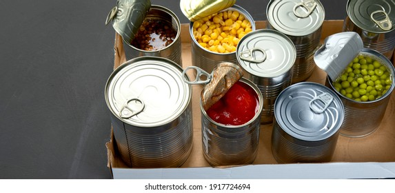 Caned vegetables such as beans, peas, corn, tomatos in cardboard box. Tin cans. Dark background. Copy space, panorama banner