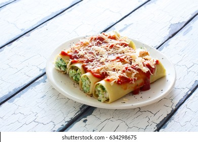 Caneloni stuffed with ricotta and spinach on white plate over grunge wood background