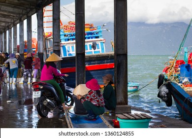 CANG CA VINH LUONG, NHA TRANG, KHANH HOA PROVINCE, VIETNAM - February 05, 2017: Fish market on the pier, women-fishmongers in simple clothes and rubber boots sit and talk after a working day