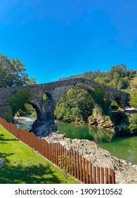 "Cangas de Onis, Spain - September 4, 2020: The Roman Bridge of Cangas de Onís, the ""Puente Vieyu"" or ""Puentón"". Medieval stone bridge over the Sella River, Asturias, Spain."