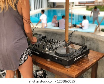 Canggu, Bali - December 15, 2018: Female DJ making music on a turntable at an opening party of a new club near the pool