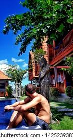 Canggu - Bali, Indonesia - 06 08 2019: Young man sitting at a pool in a beautiful hotel complex in Canggu, Bali